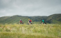 Three people cycling the Otago Central Rail Trail towards Middlemarch, South Island, New Zealand
