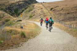 Three people cycling the Otago Central Rail Trail with Rockfall Hazard sign by the track side, at Daisybank, between Waipiata and Middlemarch, South Island