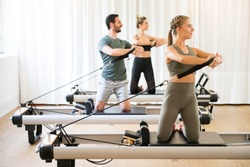 Three people exercising torson rotation at gym using pilates reformer beds