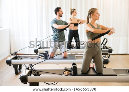 Three people exercising torson rotation at gym using pilates reformer beds Stockfoto ©