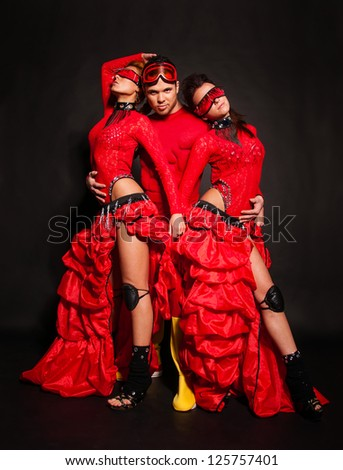 Three people in red on a black background