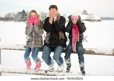 three people in snow showing speak, see and hear no evil