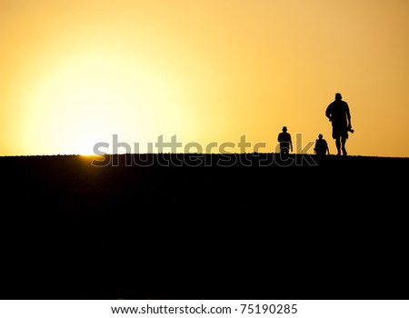 Three people in the desert silhouetted against an orange sunset