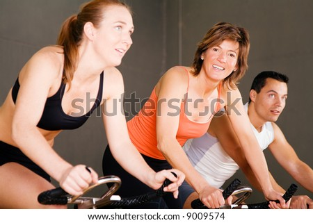 Three people in the gym, focus on the smiling woman in the middle