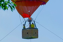 Three people in the hot air balloon nacelle. The balloon is tied to the ground