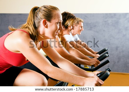 Three people on bicycles in a gym or fitness club for a workout