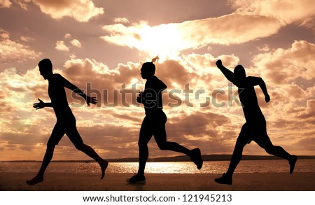 Three  people one Female and two boys runner full length silhouette against the blue sky and sun