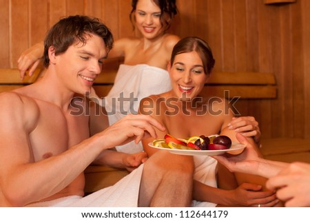 Three people (one male, two female) enjoying a hot sauna, eating some fruits