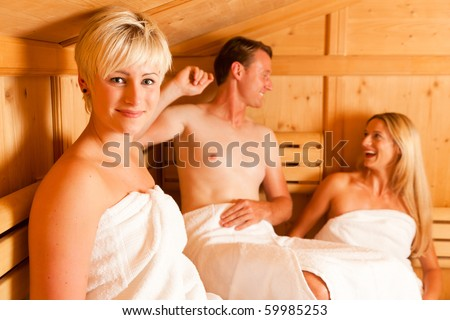 Three people (one male, two female) enjoying a hot sauna, having a casual chat
