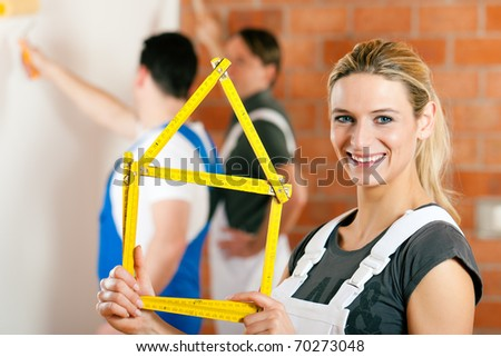 Three people - one woman and two men � renovating an apartment and having lots of fun