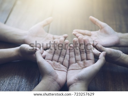 Three people pray and praising God together over wooden table with the light from above, copy space. - Shutterstock ID 723257629