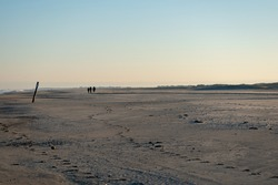 Three people walking on a sandy shore of Norderney