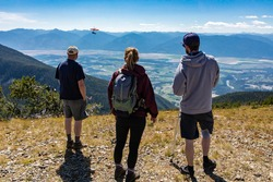 Three people watching a hang-glider pilot soaring flight over the Kootenay valley mountains, in Creston, British Columbia, Canada