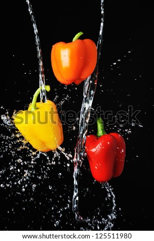 Three peppers water splash on black