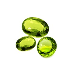Three peridot or chrysolite gems on a white background
