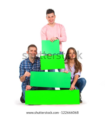 Three persons holding green tree shaped papers - stock photo