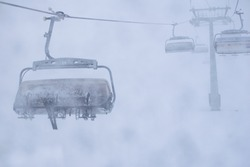 Three persons in skis sit on ski resort chair lift in stormy winter conditions.Bad visibility and weather in ski resort concept.