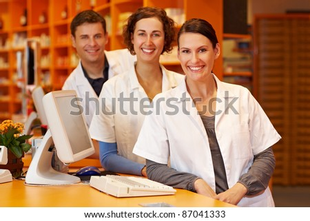 Three pharmacists at a counter in a pharmacy