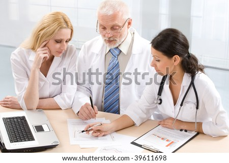 Three  physicians discuss the results of treatment - stock photo