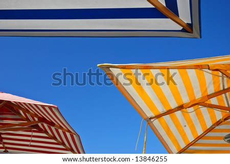 Three picnic table umbrellas in different colors outdoors set against a clear blue sky - stock photo