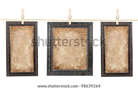 Three picture frames with aged paper isolated on a clothes line