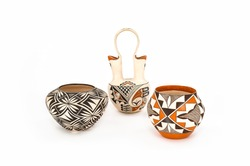 Three pieces of authentic Native American Pottery with a white background. Bright colors and intricate patterns.