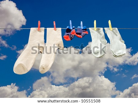 Three pieces of clothing of various size including baby on a line drying in the sun