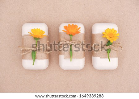 Three pieces of handmade natural soap set decorated with craft paper, scourge and orange calendula flowers. Organic cosmetics, zero waste, eco friendly concept. Top view Flat lay Copy space.