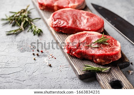 Three pieces of traditional thin steak cut from the tenderloin on wooden cutting board with olive oil, salt, rosemary and pepper. Raw Black Angus Prime meat steaks suitable for grilling or frying pan.