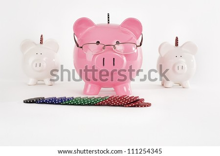 Three piggy banks with playing poker chips