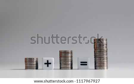 Three pile of coins with mathematical arithmetic symbols.
