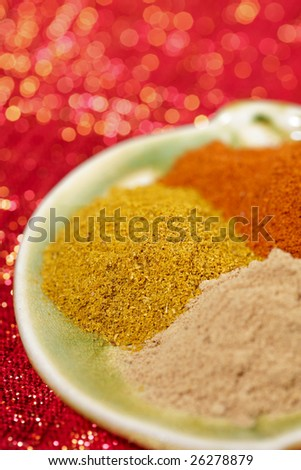 three piles of indian powder spice on plate,  Curry powder in focus, red glitter background, shallow DOF
