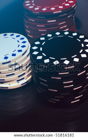 Three piles of poker chips on a reflective surface.
