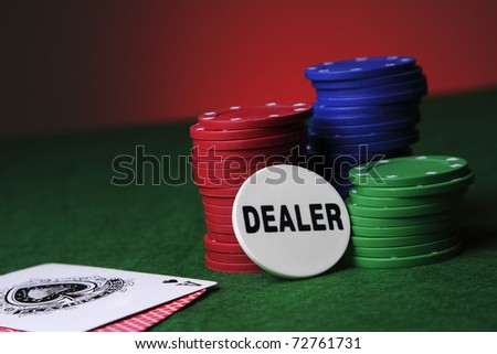 Three piles of poker chips with playing cards