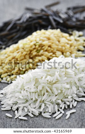Three piles of white, brown and wild black uncooked rice