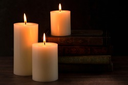 Three Pillar Candles Lit in a Dark Room with a Stack of Antique Books