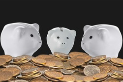 three pink ceramic piggy banks behind a bunch of copper coins on a black background