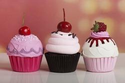 Three pink chocolate cherry strawberry cupcakes on bokeh background