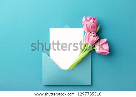 Photo of  Three pink tulips in turquoise envelope on turquoise background. Mockup with white card. Flat lay, top view.