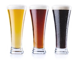 Three pints of beer, of three different colors, isolated on a white background.