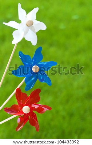 Three Pinwheels against Grass as a Fourth of July Celebration Background
