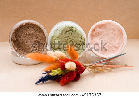 three plastic jars with coloured saline body scrub