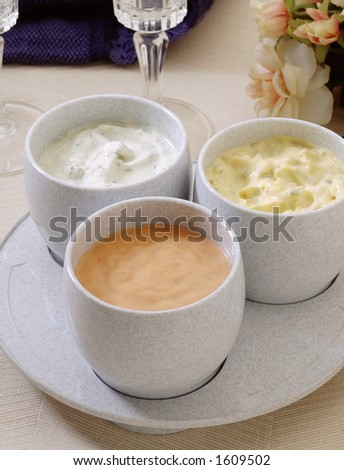 Three plastic saucers with diverse sauces