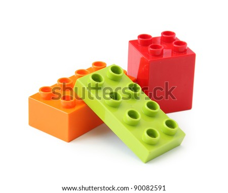 Three plastic toy blocks on white. Focus on near edge of bricks with selective focus.