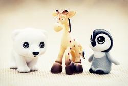 Three plastic toy figurines. Penguin, giraffe and white teddy bear.