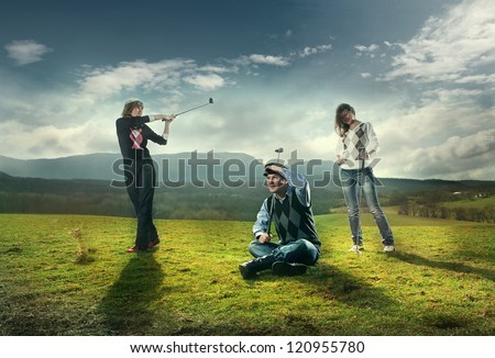 Three players play on the golf course in golf. wonderful sky formation in background.