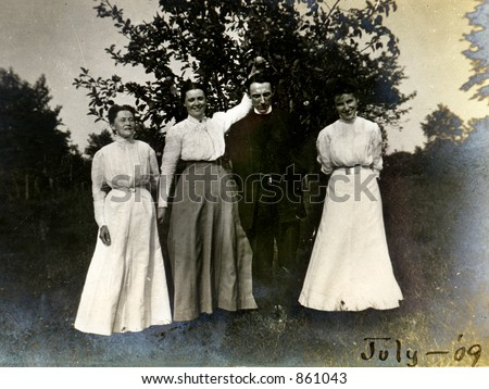 Three playful vintage women pose with a solemn preacher.  Original Circa 1909 print has scratches, artifacts, fading and solarization qualities.