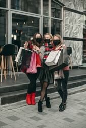 Three portrait of young happy women in medical masks and Christmas gifts walking in the city and shopping in quarantine. New year, packages, girlfriends, shop, coronavirus, pandemic