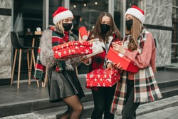 Three portrait of young happy women in red Christmas clothes, medical masks, hats and gifts walking in the city and shopping in quarantine. New year, boxes, girlfriends, shop, coronavirus, pandemic