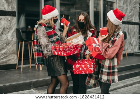 Three portrait of young happy women in red Christmas clothes, medical masks, hats and gifts walking in the city and shopping in quarantine.